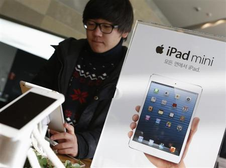 A student tries Apple Inc's iPad mini at an electronics store in central Seoul