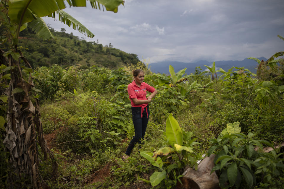 """Glenda Herrera, 34, stands at the site of her home destroyed by a landslide triggered by hurricanes Eta and Iota in the village of La Reina, Honduras, Tuesday, June 29, 2021. """"That night we ran down, I saw how the hill was coming down, but I never imagined that it would destroy everything."""" (AP Photo/Rodrigo Abd)"""
