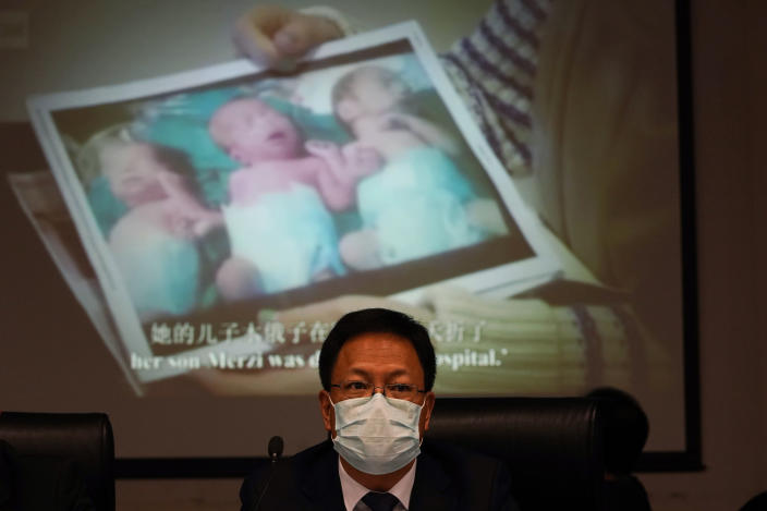 """Xu Guixiang, a deputy spokesperson for the Xinjiang regional government, looks up near a slide showing a photo of Uighur infants during a press conference to refute accusations of genocide in Beijing, China. The Chinese official on Monday denied Beijing has imposed coercive birth control measures among Muslim minority women, following an outcry over a tweet by the Chinese Embassy in Washington claiming that government polices had freed women of the Uighur ethnic group from being """"baby-making machines."""" (AP Photo/Ng Han Guan)"""