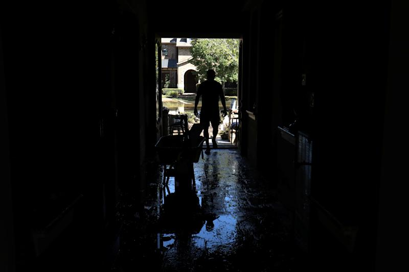 Homeowner Maurice Teixeira stands in the entrance way to his family home as he begins cleanup after floodwaters receded in the aftermath of Harvey.