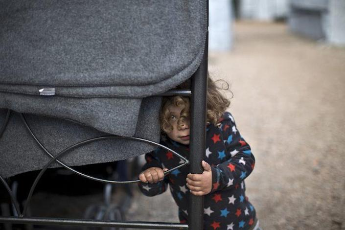 Refugee Moustafa Abdulrahman, 2, from Kobani, Syria, peeks out while standing outside his family's shelter at the refugee camp of Ritsona, about 53 miles north of Athens, Greece, on Jan. 5. (Photo: Muhammed Muheisen/AP)