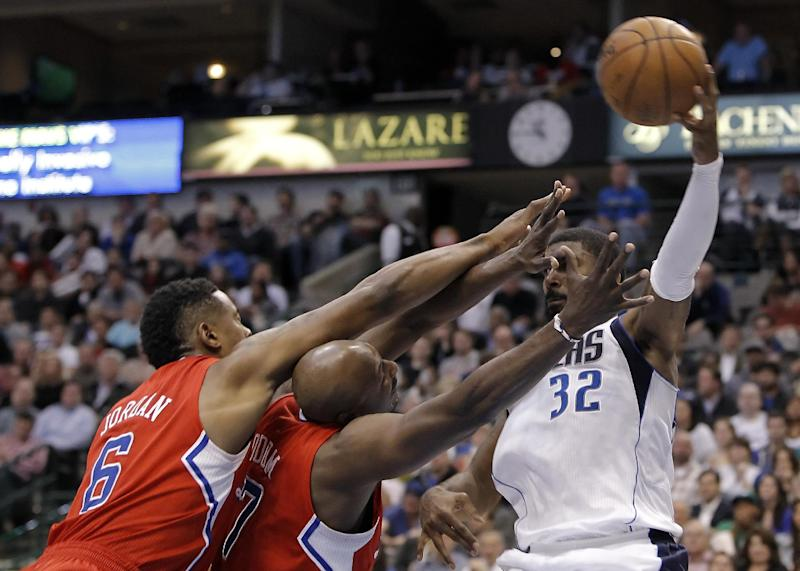 Dallas Mavericks guard O.J. Mayo (32) attempts to pass the ball as Los Angeles Clippers forwards DeAndre Jordan (6) and Lamar Odom (7) defend during the second half of an NBA basketball game, Tuesday, March 26, 2013, in Dallas. Dallas won 109-102 in overtime. (AP Photo/Brandon Wade)