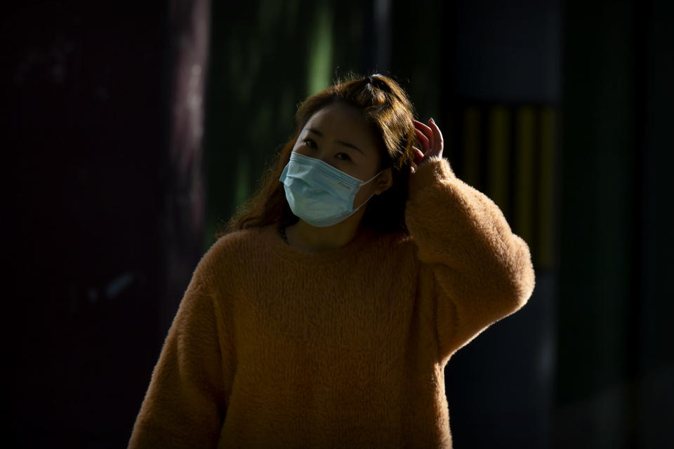 A woman wearing a face mask to protect against the coronavirus walks along a street in Beijing, Thursday, Oct. 22, 2020. The number of confirmed COVID-19 cases across the planet has surpassed 40 million, but experts say that is only the tip of the iceberg when it comes to the true impact of the pandemic that has upended life and work around the world. (AP Photo/Mark Schiefelbein)