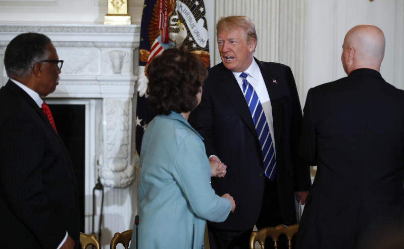 President Donald Trump is greeted by Vicksburg, Miss., Mayor George Flaggs, Jr., left, Secretary of Transportation Elaine Chao, second from left, and Nebraska Gov. Pete Ricketts, right, as he arrives for an infrastructure meeting in the State Dining Room of the White House in Washington, Monday, Feb. 12, 2018. (AP Photo/Carolyn Kaster)