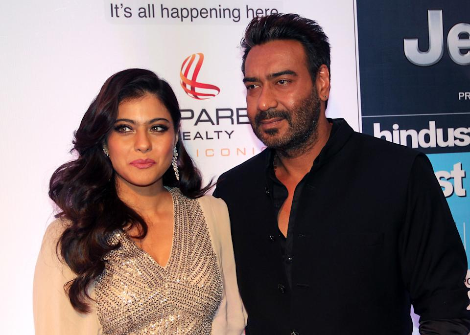 Indian Bollywood actress Kajol Devgn (L) and actor Ajay Devgn pose as they attend the