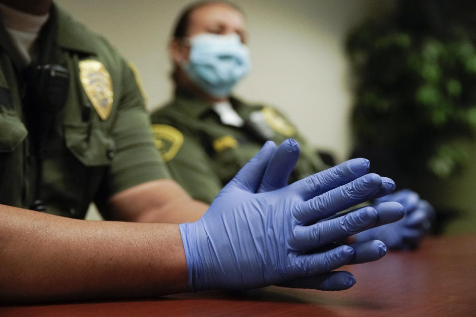 In this April 16, 2020, photo Christopher Lumpkin's gloved hands are shown during an interview at the hospital ward of the Twin Towers jail in Los Angeles. Across the country first responders who've fallen ill from COVID-19, recovered have begun the harrowing experience of returning to jobs that put them back on the front lines of America's fight against the novel coronavirus. (AP Photo/Chris Carlson)