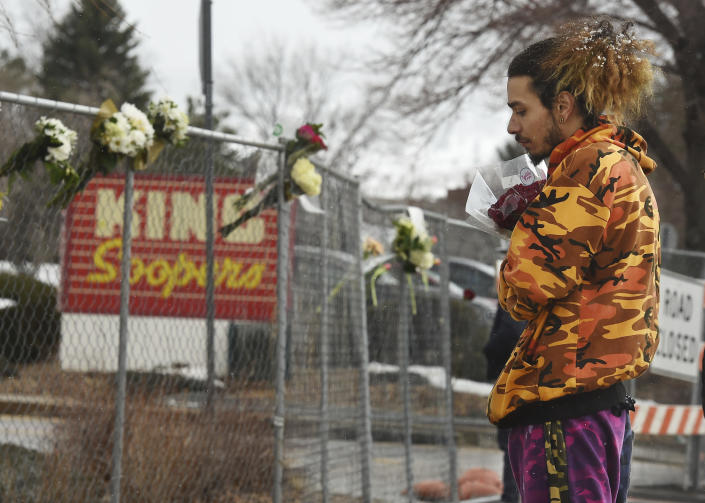 Jared Gallegos had been standing out for nearly an hour, clutching a bouquet of flowers to leave in memory of his childhood friend, Rikki Olds, on Tuesday, March 23, 2021. Rikki was shot and killed at the Boulder King Soopers on Monday in Boulder, Colorado. (Jerilee Bennett/The Gazette via AP)