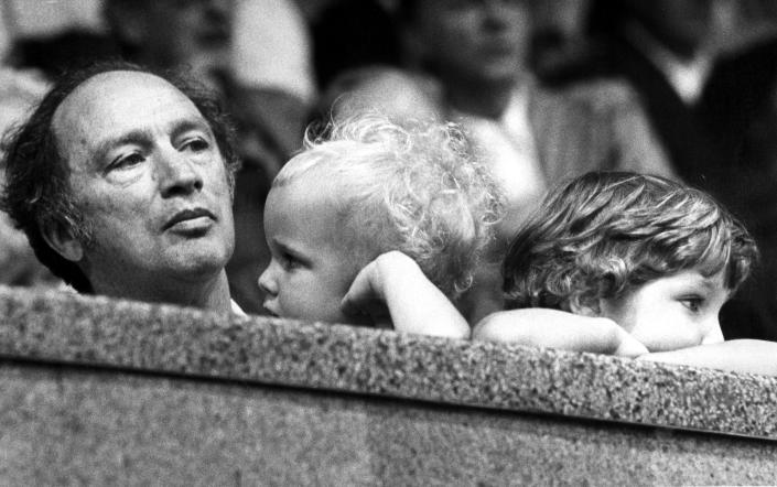 Prime Minister Pierre Trudeau watches Olympic wrestling, while his sons Alexandre, age 2, (C), and Justin, age 4, seem content to watch the crowd at the 1976 Olympics. (Credit: CP Photo)