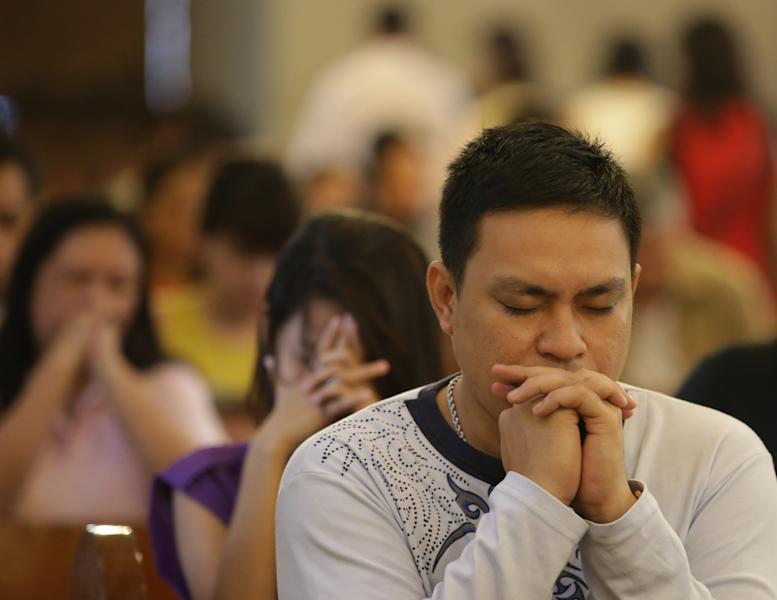"""CORRECTS MONTH- Filipino Catholics pray during a mass at the Our Lady of Remedies Parish Church in Manila, Philippines Sunday, Sept. 22, 2013. Catholics around the globe are expressing mixed but mostly positive reactions to Pope Francis' recent remarks that the church has become too focused on """"small minded rules"""" on hot-button issues like homosexuality and abortion. (AP Photo/Aaron Favila)"""