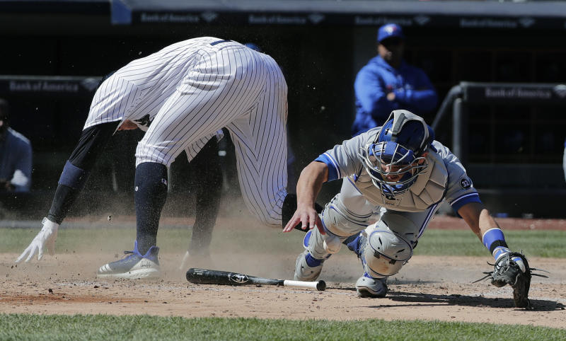 Toronto Blue Jays catcher Luke Maile drops the throw from pitcher Marcus Stroman as New York Yankees' Aaron Judge slides safely into home plate on a bases-loaded infield grounder by Aaron Hicks during the sixth inning of a baseball game, Saturday, April 21, 2018, in New York. Judge was safe on the play. (AP Photo/Julie Jacobson)