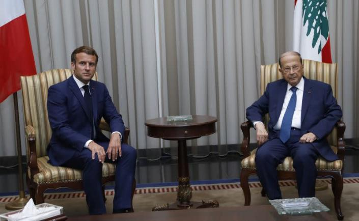 Lebanon's President Michel Aoun meets with French President Emmanuel Macron upon his arrival at the airport in Beirut
