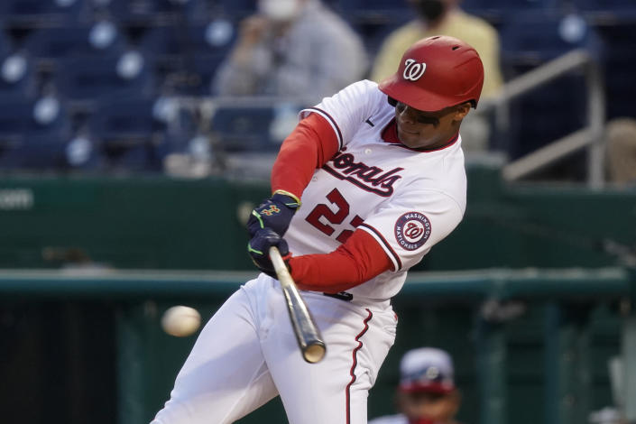 Washington Nationals' Juan Soto singles in the ninth inning of an opening day baseball game against the Atlanta Braves at Nationals Park, Tuesday, April 6, 2021, in Washington. Victor Robles scored on the play, and Washington won 6-5. (AP Photo/Alex Brandon)