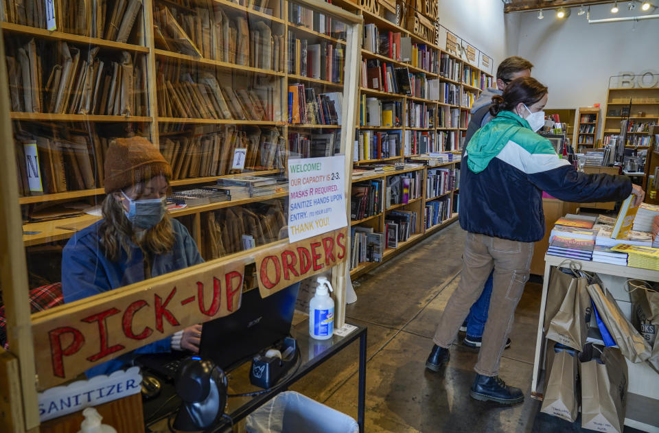 Hannah Martin works behind a plexiglass sheet, as she delivers book pickup orders at the Skylight Book store in the Los Feliz neighborhood of Los Angeles Monday, Jan. 25, 2021. California has lifted regional stay-at-home orders statewide in response to improving coronavirus conditions. Public health officials said Monday that the state will return to a system of county-by-county restrictions intended to stem the spread of the virus. Local officials could choose to continue stricter rules. The state is also lifting a 10 p.m. to 5 a.m. curfew. (AP Photo/Damian Dovarganes)