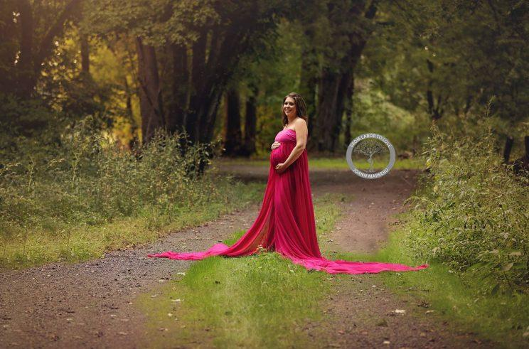 Pregnant woman in red dress stands on a road in the woods