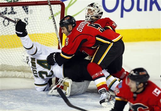 Dallas Stars' Eric Nystrom, left, gets tackled by Calgary Flames' Mark Giordano, center, in front of Flames goalie Miikka Kiprusoff, from Finland, during the first period of an NHL hockey game in Calgary, Alberta, Monday, March 26, 2012. (AP Photo/The Canadian Press, Jeff McIntosh)