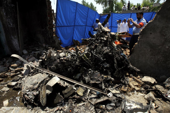 FILE - In this May 17, 2012 file photo, a Pakistan air force official, right, takes photographs of the wreckage of a plane which crashed in Nowshera, Pakistan. Over a dozen Pakistani air force planes have crashed in roughly the past 18 months, raising concerns about the health of an aging fleet that officials are struggling to upgrade because of a lack of funds. A significant number of the air force's combat aircraft are nearly half a century old and have been called on in recent years to help the army fight a domestic Taliban insurgency that has killed thousands of people. This has added to the strain on a force that has historically focused on countering the threat from Pakistan's neighbor and archenemy, India. (AP Photo/Mohammad Sajjad, File)