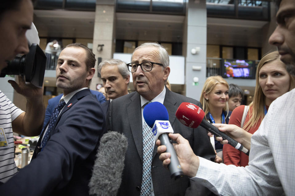 European Commission President Jean-Claude Juncker speaks to the media during an EU summit in Brussels, Friday, Oct. 18, 2019. After agreeing on terms for a new Brexit deal, European Union leaders are meeting again to discuss other thorny issues including the bloc's budget and climate change. (AP Photo/Virginia Mayo)