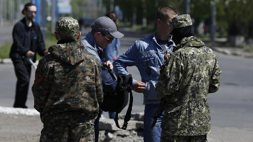 <p>Two pro-Russian armed men (front) check identity papers in the eastern Ukrainian city of Slavyansk, on April 26, 2014</p>