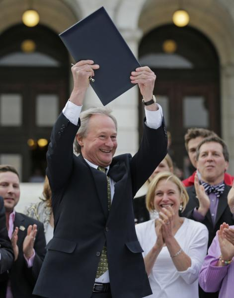 Rhode Island Gov. Lincoln Chafee holds up a a gay marriage bill after signing it into law outside the State House in Providence, R.I., Thursday, May 2, 2013. (AP Photo/Charles Krupa)