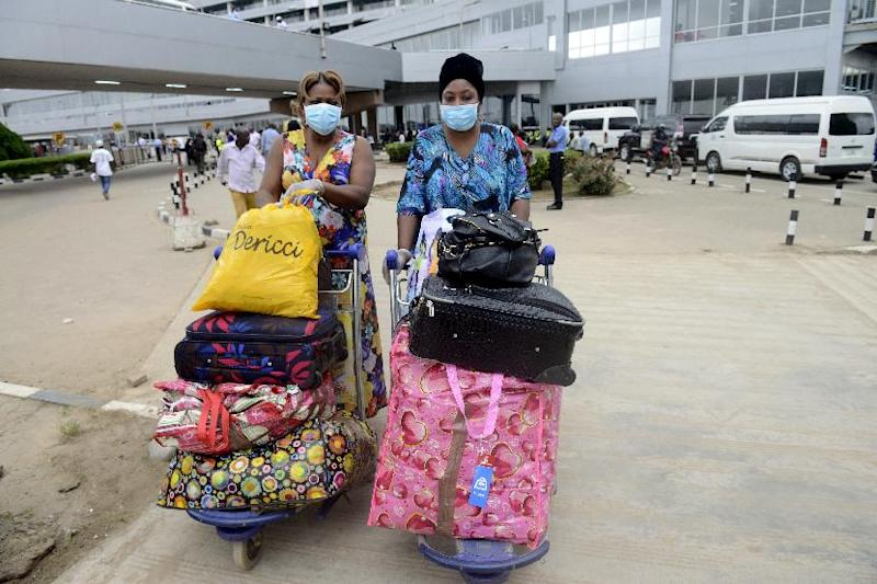 Passengers wearing protective face masks and gloves arrive at the Murtala Mohammed Airport in Lagos on August 11, 2014