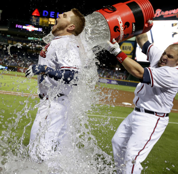 Atlanta Braves' Freddie Freeman, left, is doused with water by Eric Hinske after Freeman hit a home run in the ninth inning as the Braves beat the Marlins 4-3 to clinch at least an NL wild-card playoff berth Tuesday, Sept. 25, 2012, in Atlanta. (AP Photo/David Goldman)