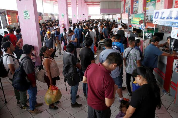 People queue to buy tickets at a bus station after Peru's government deployed military personnel to block major roads, as the country rolled out a 15-day state of emergency to slow the spread of coronavirus disease (COVID-19), in Lima