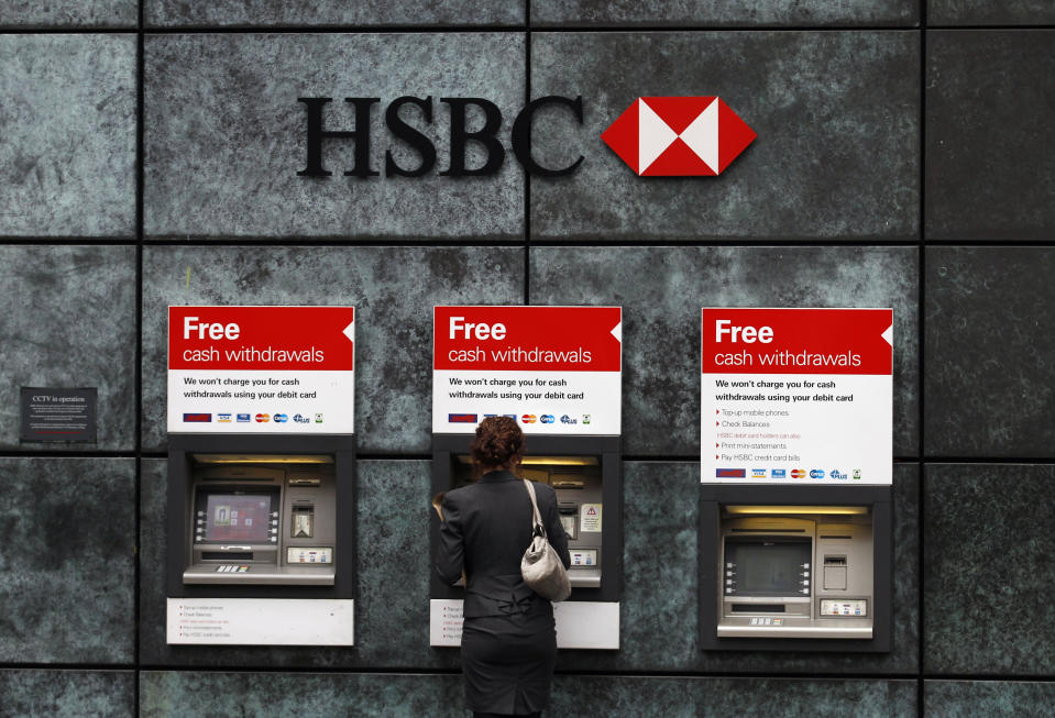 A woman uses a cash point machine at a HSBC bank in the City of London February 28, 2011. HSBC cut its profitability targets due to the cost of tougher banking regulations, joining rivals such as Barclays, and disappointed investors with below forecast 2010 earnings.    REUTERS/Andrew Winning (BUSINESS)