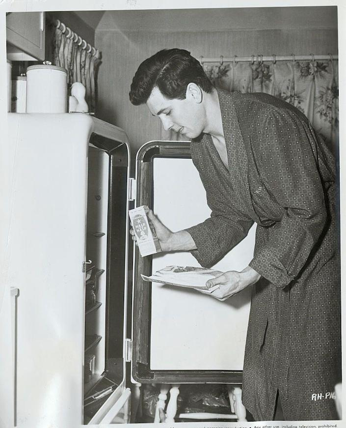 """<p>Hudson, as seen here shuffling through a refrigerator, landed his first big-screen roles in the early 1950s, but the actor really took off following his part in the breakout movie <em>Magnificent Obsession</em> in 1954.</p><p><strong>RELATED: </strong><a href=""""https://www.womansday.com/life/g36710040/rock-hudson-photos/"""" rel=""""nofollow noopener"""" target=""""_blank"""" data-ylk=""""slk:Rock Hudson's Life in Photos"""" class=""""link rapid-noclick-resp"""">Rock Hudson's Life in Photos</a> </p>"""