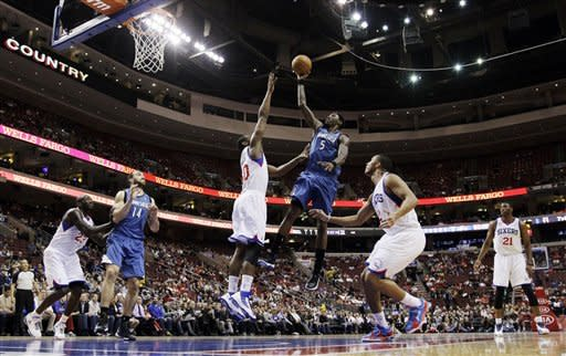 Minnesota Timberwolves' Josh Howard (5) shoots between Philadelphia 76ers' Lavoy Allen (50) and Evan Turner (12) in the first half of an NBA basketball game, Tuesday, Dec. 4, 2012, in Philadelphia. (AP Photo/Matt Slocum)