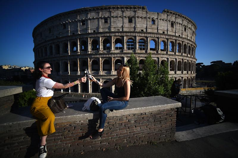 Young women share an aperitif drink by the Colosseum in Rome on May 21, 2020, after the country eases its two-month lockdown. (Photo: FILIPPO MONTEFORTE via Getty Images)