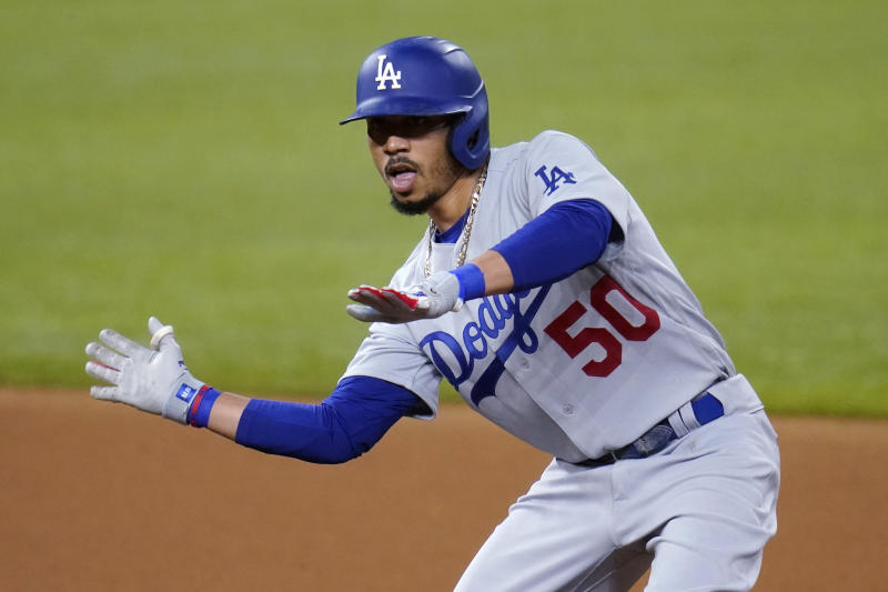 Los Angeles Dodgers' Mookie Betts (50) gestures after his double against the San Diego Padres during the fourth inning in Game 3 of a baseball National League Division Series Thursday, Oct. 8, 2020, in Arlington, Texas. (AP Photo/Sue Ogrocki)