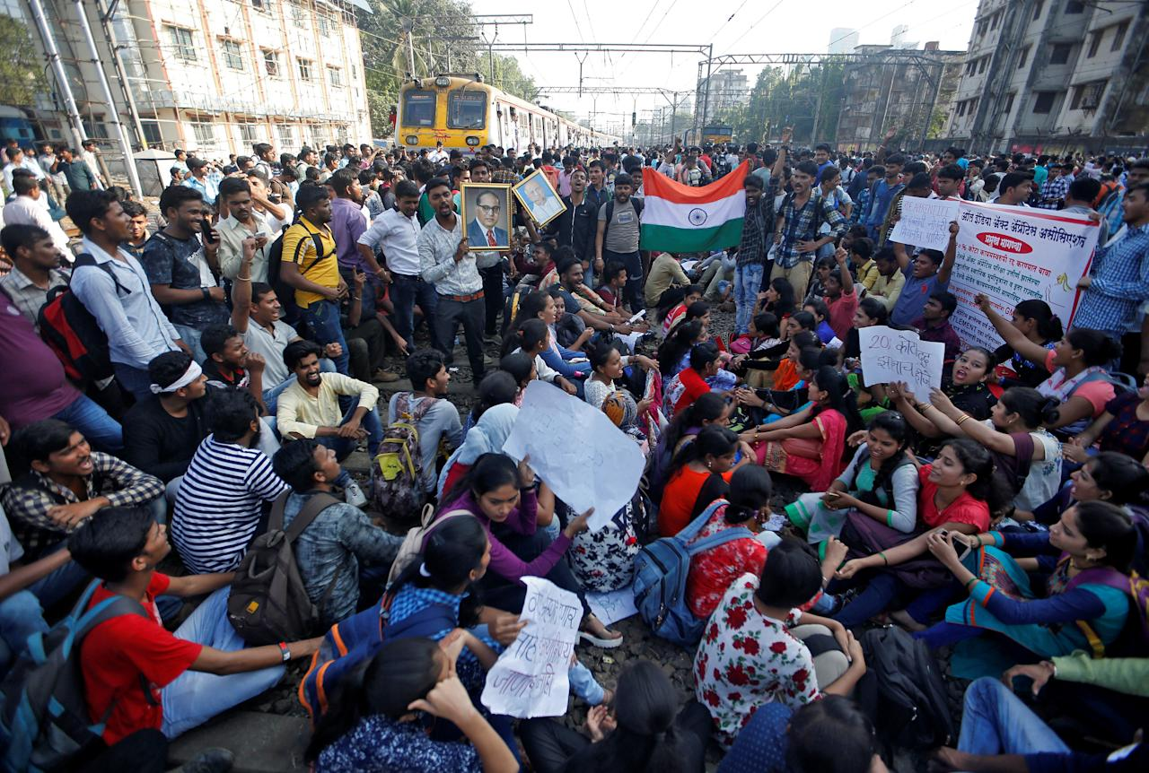 People sit on railway tracks as they block train services during a protest demanding recruitment into the railway services in Mumbai, India, March 20, 2018. REUTERS/Francis Mascarenhas