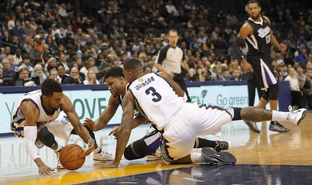 Memphis Grizzlies guard Mike Conley, left, and forward James Johnson (3) fight for a loose ball with Sacramento Kings forward Rudy Gay, center, in the first half of an NBA basketball game on Friday, Jan. 17, 2014, in Memphis, Tenn. (AP Photo/Lance Murphey)