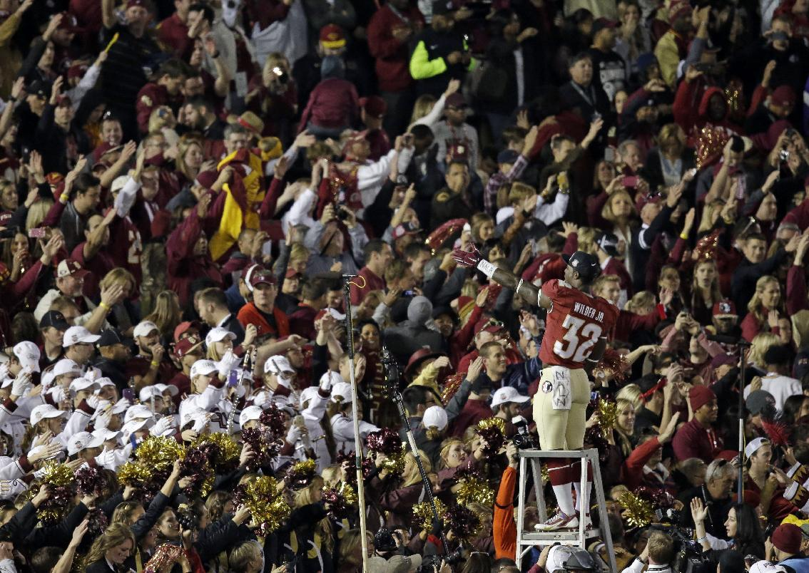 Florida State's James Wilder Jr. (32) celebrates with fans after the NCAA BCS National Championship college football game against Auburn Monday, Jan. 6, 2014, in Pasadena, Calif. Florida State won 34-31. (AP Photo/Gregory Bull)