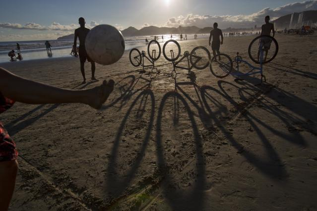 "Using bicycles as a ""net"", kicking a ball back and forth at the beach Santos, Brazil. (David Guttenfelder/AP Images for The New York Times Magazine)"