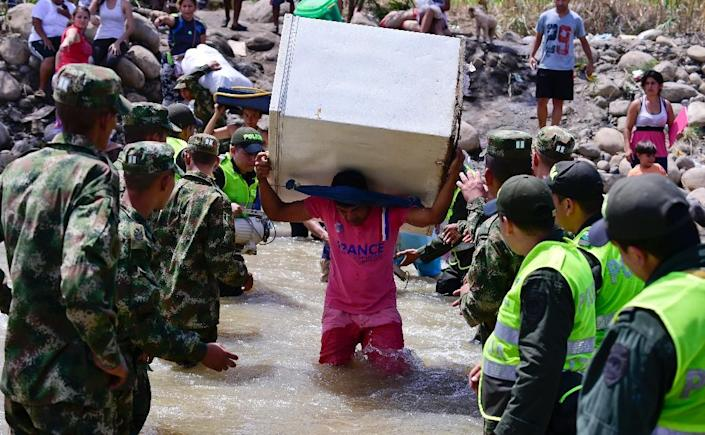 Colombians leaving Venezuela with their belongings cross the Tachira River to arrive in Cucuta, Colombia, on August 27, 2015 (AFP Photo/Luis Acosta)