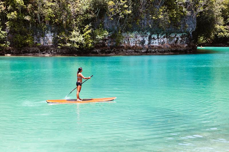 Beautiful woman practising stand up paddling, Siargao, Philippines as Cebu Pacific drops flights from Australia to $139