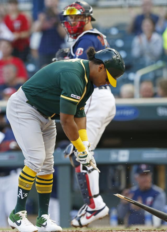 Oakland Athletics' Khris Davis breaks his bat slamming it on the ground after striking out to Minnesota Twins pitcher Jose Berrios in the first inning of a baseball game Saturday, July 20, 2019, in Minneapolis. Looking on is Twins catcher Mitch Garver. (AP Photo/Jim Mone)