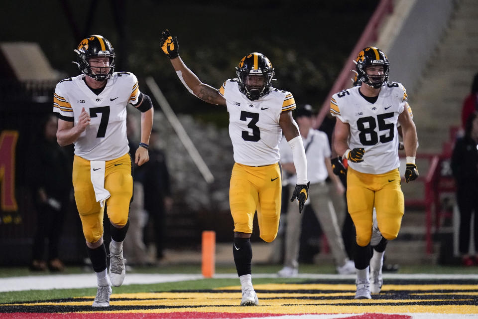 Iowa wide receiver Tyrone Tracy Jr. (3) celebrates his touchdown catch on a pass from quarterback Spencer Petras (7) during the second half of an NCAA college football game against Maryland, Friday, Oct. 1, 2021, in College Park, Md. Iowa defensive lineman Logan Lee runs along. (AP Photo/Julio Cortez)
