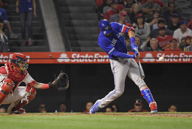 Toronto Blue Jays' Lourdes Gurriel Jr., right, hits a solo home run in front of Los Angeles Angels catcher Martin Maldonado during the seventh inning of a baseball game Thursday, June 21, 2018, in Anaheim, Calif. (AP Photo/Mark J. Terrill)