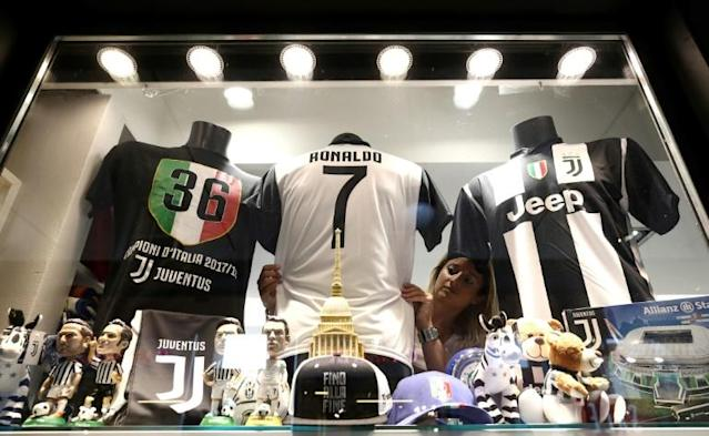 A saleswoman makse up a shop window with Cristiano Ronaldo's Juventus jersey in downtown Turin a day after the Portuguese football superstar transfered from Real Madrid to Italy's Juventus (AFP Photo/Isabella Bonotto)