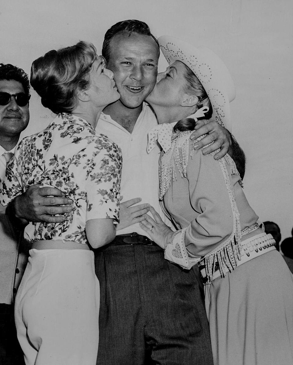 <p>Professional golfer Arnold Palmer scores a celebratory kiss on the cheek from actresses Debbie Reynolds (right) and Gail Davis (left) after winning the Desert Classic golf tournament. </p>
