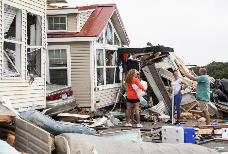 Residents of the Boardwalk RV Park in Emerald Isle, N.C., discuss the path of Hurricane Dorian's waterspout after it ripped through their community on Thursday, Sept. 5, 2019. (Julia Wall/Raleigh News & Observer/Tribune News Service via Getty Images)