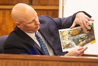 Massachusetts State Trooper Stephen Gallagher holds a picture of a small handgun found in a wooded area near the crime scene during the murder trial of the former New England Patriots player Aaron Hernandez at the Bristol County Superior Court in Fall River, Massachusetts February 13, 2015. REUTERS/Aram Boghosian/Pool (UNITED STATES - Tags: CRIME LAW SPORT FOOTBALL)