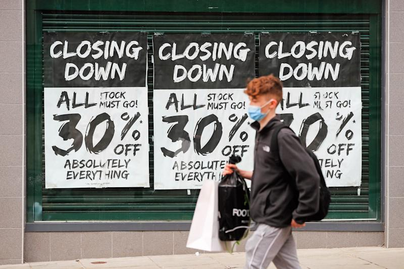 A man wearing a protective face mask walks past a shop window advertising a closing down sale in Nottingham city centre: PA