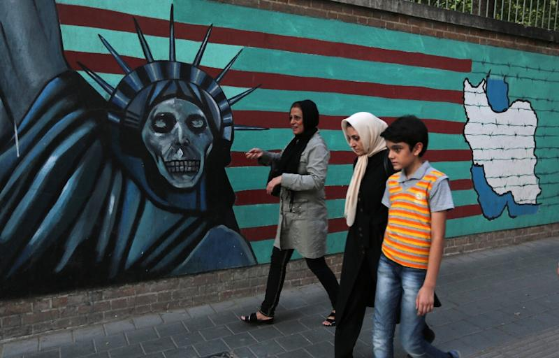 An Iranian family walks past anti-US graffiti on the wall of the former US embassy in Tehran on July 14, 2015 (AFP Photo/Atta Kenare)