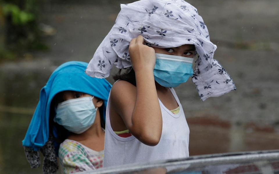 Young girls wearing masks place clothes on their heads to shelter them from rain due to Typhoon Molave in Pampanga province, northern Philippines - AP