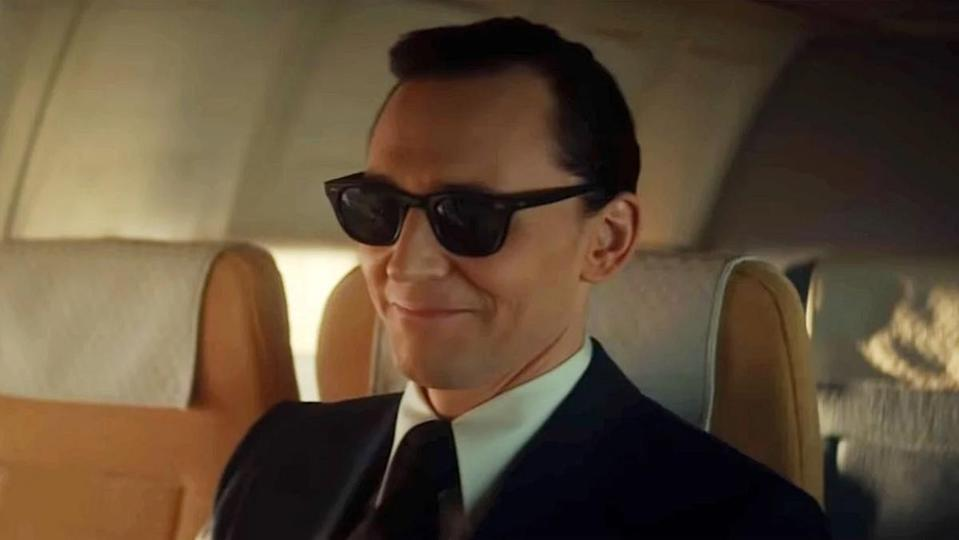 Tom Hiddleston as Loki dressed in a snappy suit, slicked hair, and sunglasses aboard a 1971 airplane assaying the infamous hijacker D.B. Cooper.