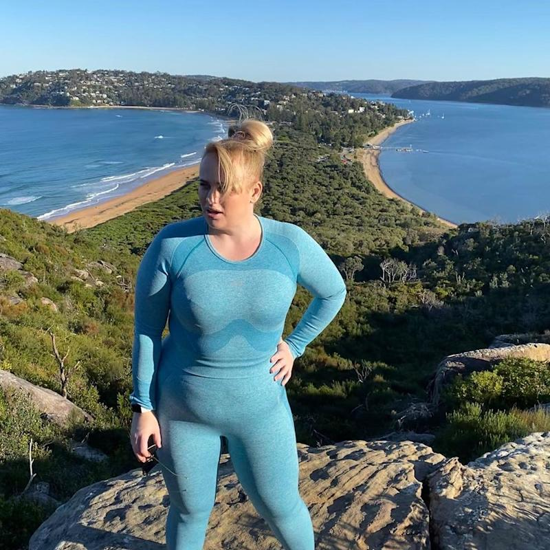 Rebel Wilson posing in blue workout outfit