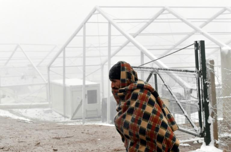 A migrant walks past what remains of the tents of the 'Lipa' migrant camp in Bosnia, two weeks after it burnt down. Hundreds of migrants are waiting for new shelters